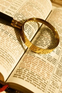 Open Bible with magnifying glasss
