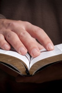 Hand on the pages of a Bible